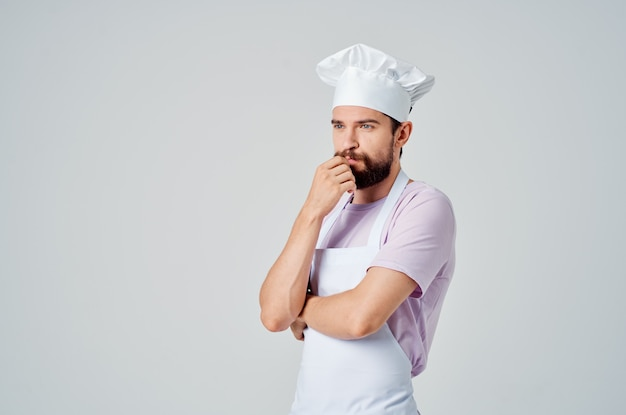 Chef masculin barbu dans les restaurants d'ustensiles de cuisine de tablier blanc