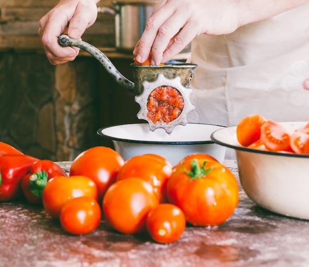 Chef masculin broie des morceaux de tomates mûres dans un vieux moulin vintage pour faire une sauce maison