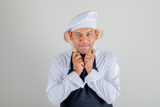 Chef masculin en chapeau, tablier et uniforme tenant des cuillères en bois tout en s'amusant et en regardant amusant