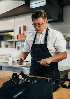 Chef masculin contrôle le presse-papiers dans la cuisine