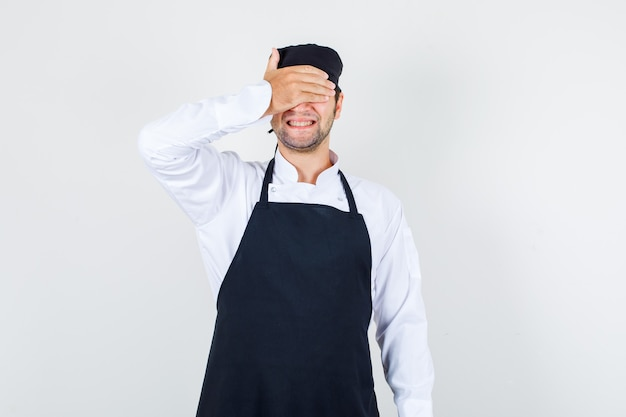 Chef masculin couvrant les yeux avec la main en uniforme, tablier et à la recherche d'excité. vue de face.