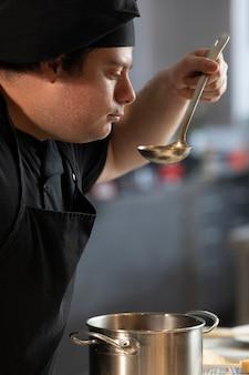 Chef masculin dans la cuisine, dégustation de la nourriture