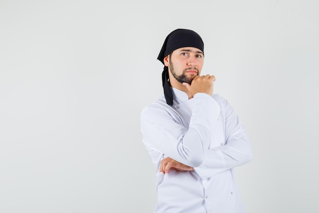 Chef masculin debout en pensant pose en uniforme blanc et à la recherche de sens. vue de face.