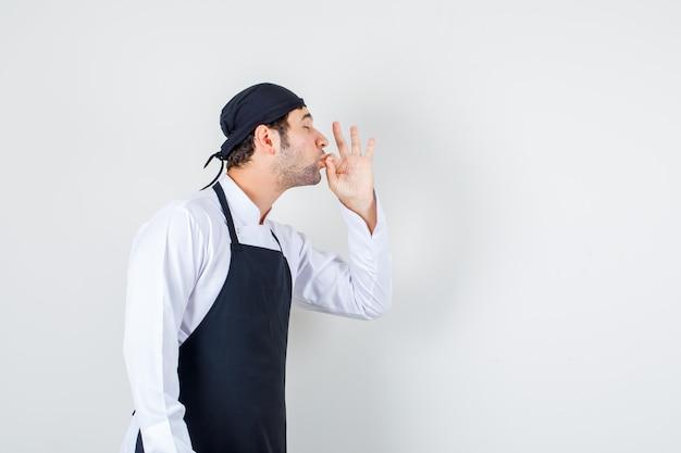 Chef masculin faisant un geste délicieux en uniforme, tablier. vue de face.
