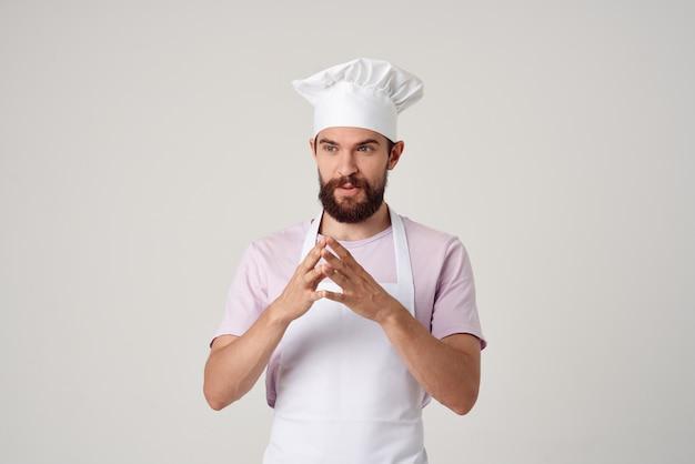 Un chef masculin gai dans un tablier blanc fait des gestes avec sa cuisine de restaurant de mains aux professionnels