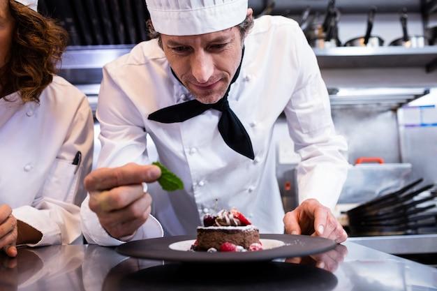 Chef masculin garnissant son dessert avec une feuille de menthe sur le comptoir