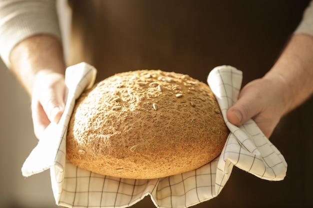 Chef masculin avec miche de pain, gros plan