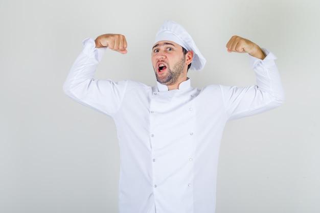 Chef masculin montrant ses muscles en uniforme blanc et à la forte