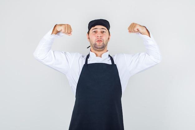 Chef masculin montrant ses muscles en uniforme, tablier et à la confiance. vue de face.