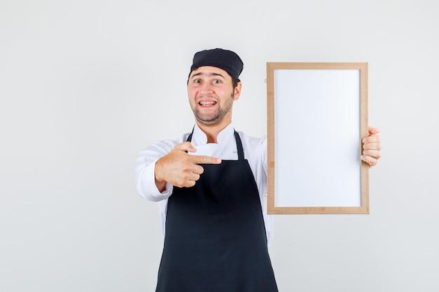 Chef masculin pointant le doigt sur le tableau blanc en uniforme, tablier et à la gaieté. vue de face.