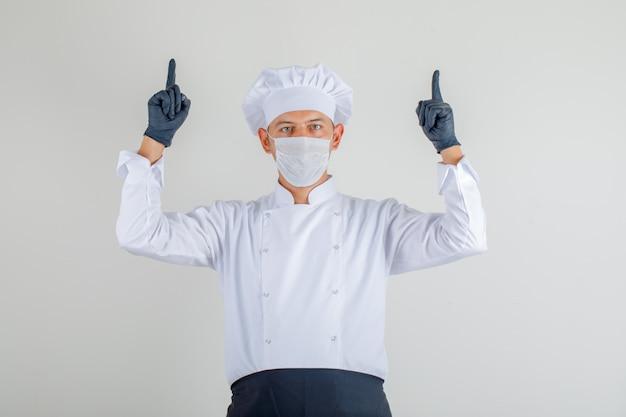 Chef masculin pointant les doigts en uniforme, tablier et chapeau et regardant prudemment