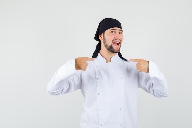 Chef masculin pointant sur lui-même en uniforme blanc et l'air fier. vue de face.