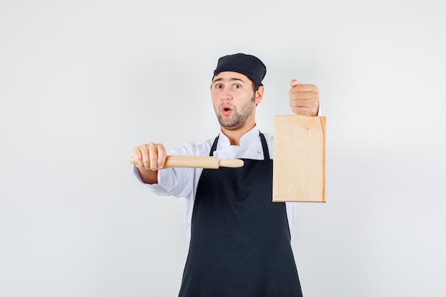 Chef masculin pointant le rouleau à pâtisserie sur une planche à découper en uniforme, tablier, vue de face.