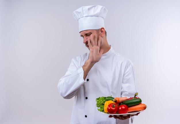 Chef masculin professionnel cuisinier en uniforme blanc et cook hat tenant une assiette avec des légumes, faisant un geste de défense avec la main debout sur fond blanc