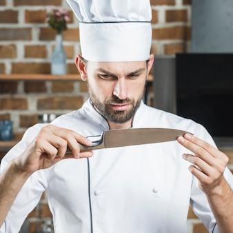 Chef masculin en regardant couteau pointu