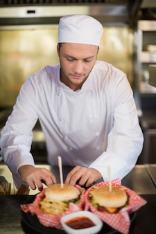 Chef masculin sérieux prépare un hamburger dans une cuisine commerciale