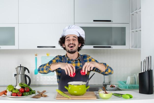 Chef masculin souriant et heureux avec des légumes frais ajoutant des poivrons rouges au repas dans la cuisine blanche