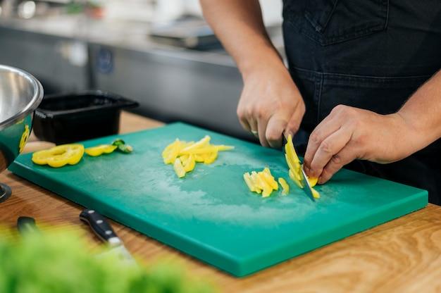 Chef masculin avec tablier, trancher les légumes dans la cuisine