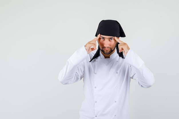 Chef masculin tenant les doigts sur les tempes en uniforme blanc et semblant sérieux, vue de face.