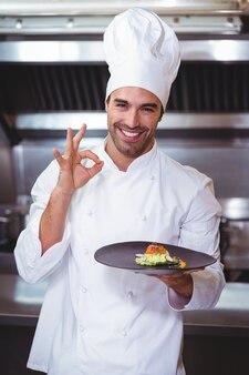 Chef masculin tenant la plaque et faisant signe ok