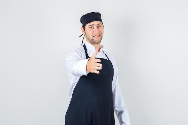 Chef masculin tendant la main pour saluer en uniforme, tablier et à la recherche de jovial. vue de face.