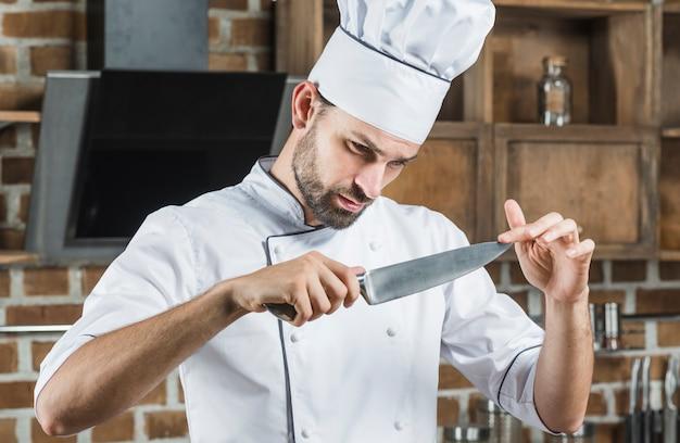 Chef masculin touchant la netteté du couteau