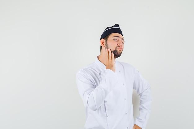 Chef masculin touchant sa barbe en uniforme blanc et ayant l'air confiant. vue de face.