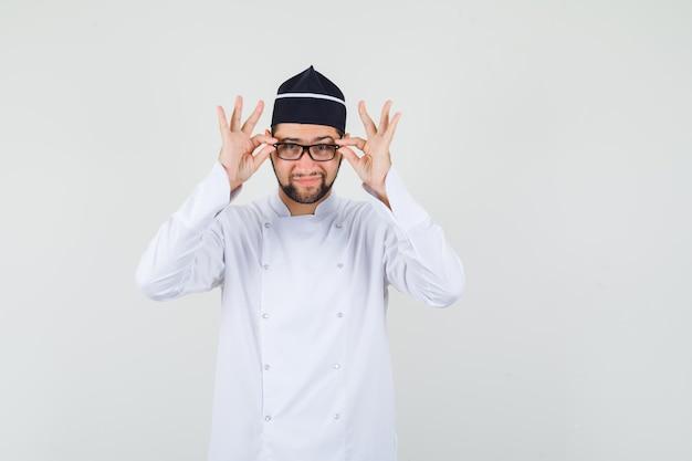 Chef masculin touchant ses lunettes en uniforme blanc et ayant l'air positif. vue de face.