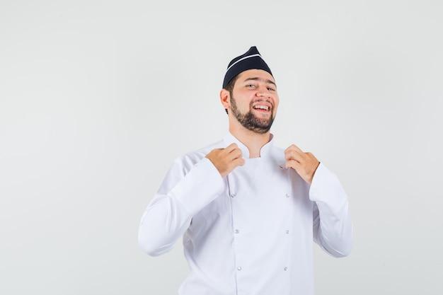 Chef masculin touchant son uniforme avec les mains en uniforme blanc, chapeau et l'air confiant. vue de face.