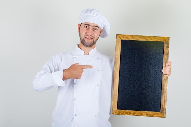 Chef masculin en uniforme blanc montrant le tableau noir avec le doigt et à la recherche positive
