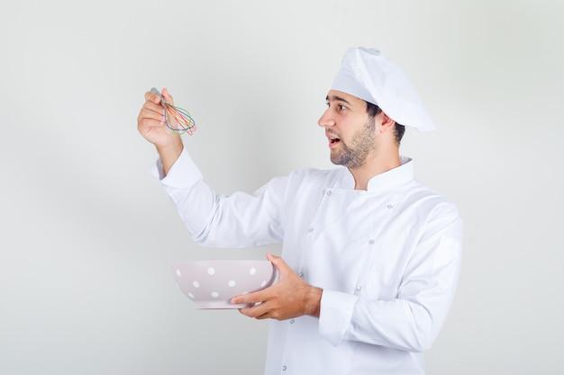 Chef masculin en uniforme blanc tenant un fouet et un bol