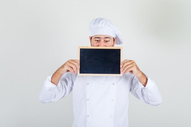 Chef masculin en uniforme blanc tenant et regardant le tableau noir