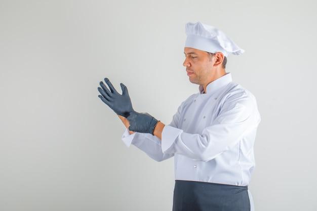 Chef masculin en uniforme, tablier et chapeau portant des gants et regardant prudemment