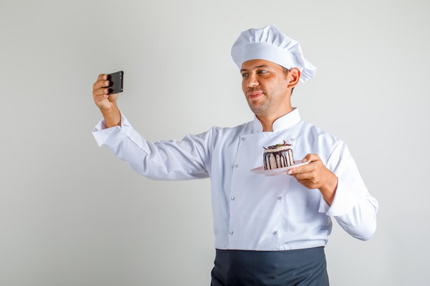 Chef masculin en uniforme, tablier et chapeau prenant selfie avec gâteau au dessert