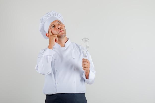 Chef masculin en uniforme, tablier et chapeau tenant un fouet et penser et regarder prudemment