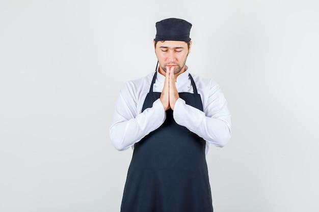 Chef masculin en uniforme, tablier main dans la main en geste de prière et à la vue de face, silencieux.