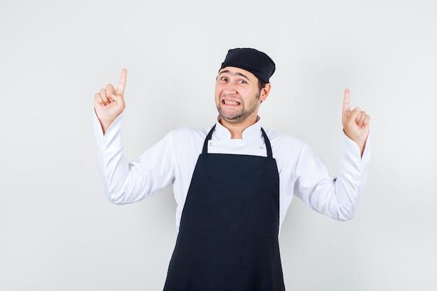 Chef masculin en uniforme, tablier pointant vers le haut les doigts avec les dents serrées et à la peur, vue de face.
