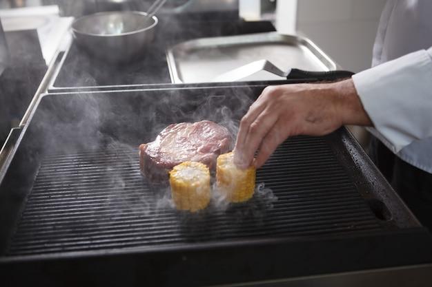 Chef méconnaissable cuisinant du boeuf et du maïs sucré sur un gril