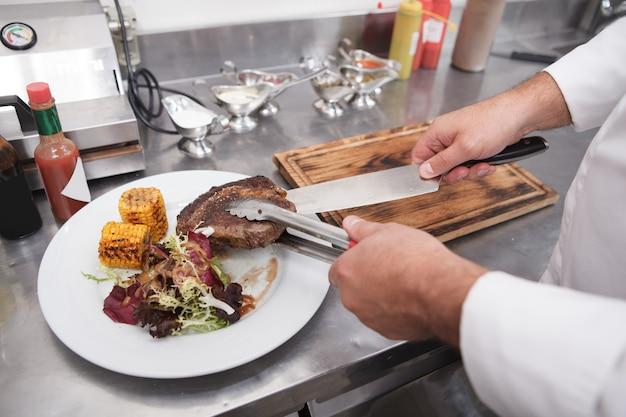 Chef méconnaissable préparant un steak de boeuf avec de la salade