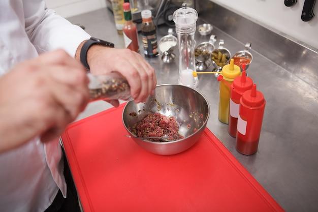 Chef méconnaissable salant la viande de boeuf hachée pour le tartre