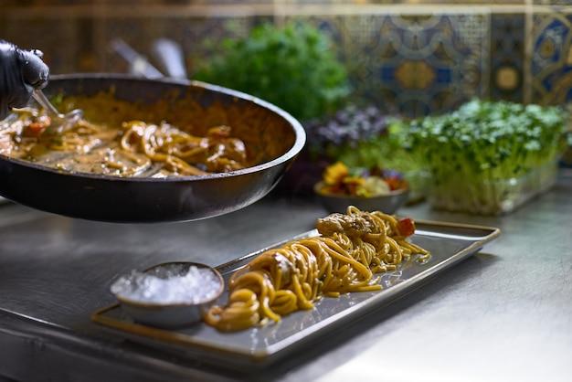Le chef mélange les spaghettis dans une casserole de tomates et d'huîtres, dans un restaurant.