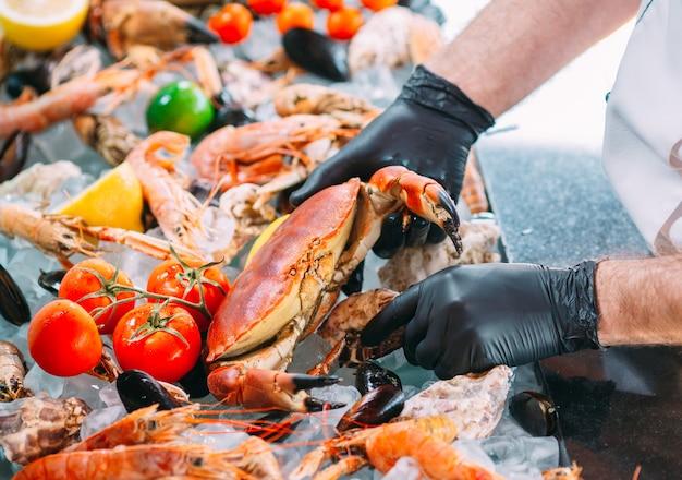 Le chef met les fruits de mer sur un plateau dans le restaurant.