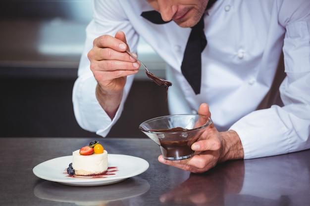 Chef mettant une sauce au chocolat sur un dessert