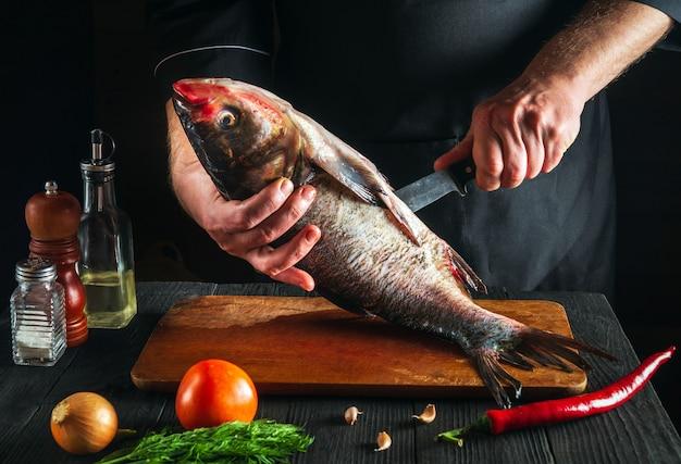 Le chef nettoie un poisson carpe à grosse tête. environnement de travail dans la cuisine du restaurant. concept de régime de poisson.