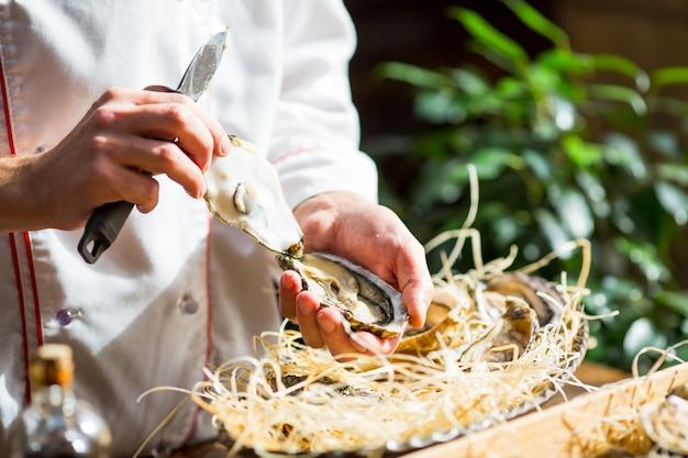 Chef ouvre huîtres fraîches dans un restaurant