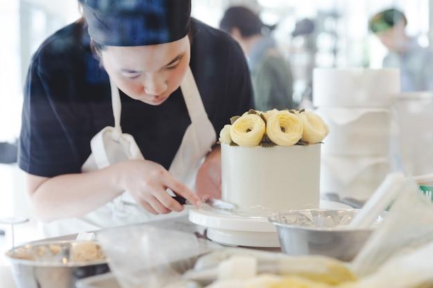 Chef pâtissier faisant une fleur de beurre jaune pour la décoration de gâteaux.