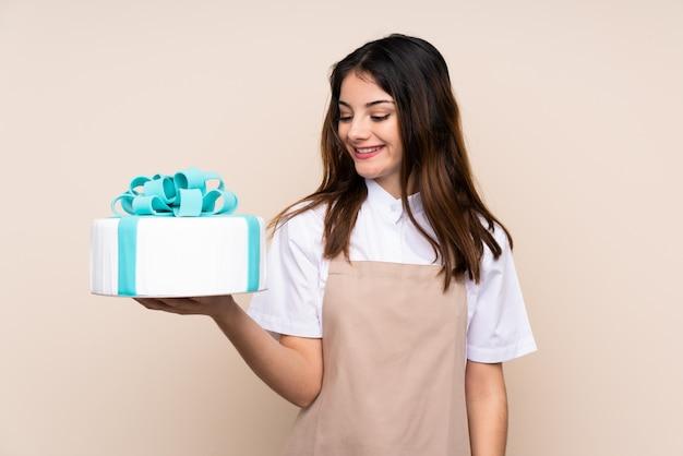 Chef pâtissier femme tenant un gros gâteau sur le mur avec une expression heureuse