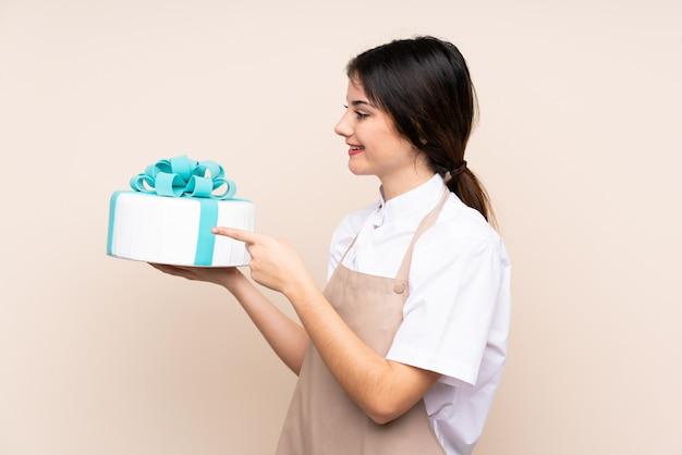 Chef pâtissier femme tenant un gros gâteau sur le mur pointant vers le côté pour présenter un produit