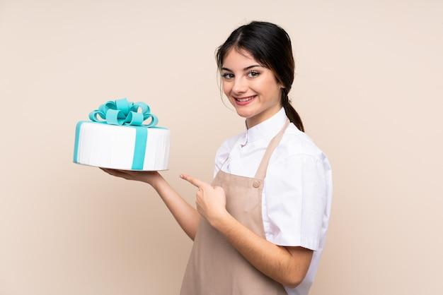 Chef pâtissier femme tenant un gros gâteau sur le mur et en le pointant