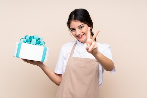 Chef pâtissier femme tenant un gros gâteau souriant et montrant le signe de la victoire